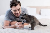Photo handsome man playing with funny raccoon on bedding at home