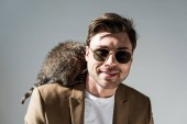 Photo smiling man in sunglasses with furry raccoon on shoulder on grey