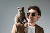 cheerful man in sunglasses with funny raccoon on shoulder on grey
