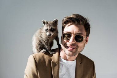 smiling man in sunglasses with cute raccoon on shoulder on grey
