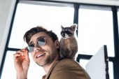 Photo funny raccoon sitting on shoulder of handsome smiling man in sunglasses