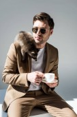 handsome man holding coffee cup, with cute raccoon on shoulder