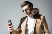 Fotografie good-looking man, with adorable raccoon on shoulder, taking selfie with smartphone on grey