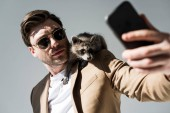 Fotografie selective focus of handsome man with adorable raccoon on shoulder, taking selfie with smartphone on grey