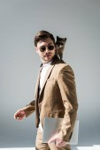 Photo handsome man with adorable raccoon on shoulder holding laptop on grey