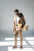 handsome man with adorable raccoon on shoulder holding longboard on grey