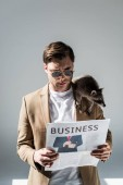 Fotografie concentrated man with funny raccoon on shoulder reading business newspaper