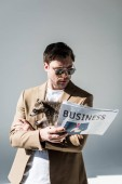 attentive man in sunglasses, with funny raccoon on shoulder, reading business newspaper