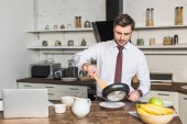 Fényképek jóképű ember a serpenyőben sütés előkészítése reggeli mellett áll a konyhaasztal