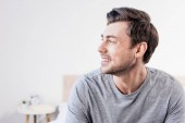handsome man in grey t-shirt smiling and looking away at home
