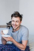 smiling man with funny raccoon on shoulder holding coffee cup while sitting on bedding