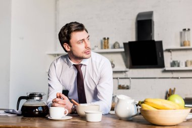 handsome pensive man standing by kitchen table and looking away