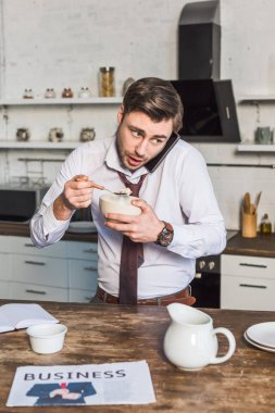 handsome man having breakfast and talking in smartphone in kitchen at home
