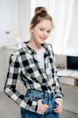 Confident teenage kid in checkered shirt looking at camera with smile