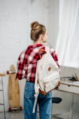 Back view of teenager in checkered shirt and jeans with backpack