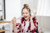 Excited teenager in checkered shirt and headphones smiling during video call
