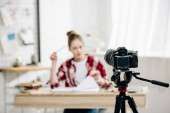 Teenage blogger ül íróasztalon előtt videokamerát, és hogy a videó