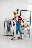 Full length view of teenager in jeans and checkered shirt standing on longboard in bedroom
