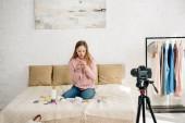 Tizenéves gyerek farmerben ül ágyon kozmetikumok előtt videokamera