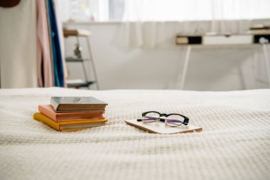 Books and glasses on bed in light cozy bedroom
