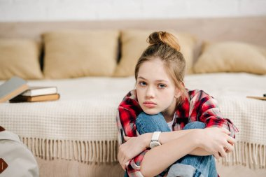 Bored teenager in checkered shirt sitting near bed and embracing knees