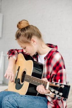 Concentrated teenager in checkered shirt playing acoustic guitar at home