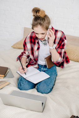 Worried teenager sitting on bed with books and laptop and talking on smartphone