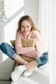 Smiling teenage kid embracing brown cushion and looking at camera