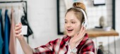 Panorama shot of teenager in headphones waving hand during video call