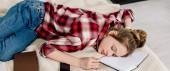 Panoramic shot of sleeping teenager in red checkered shirt