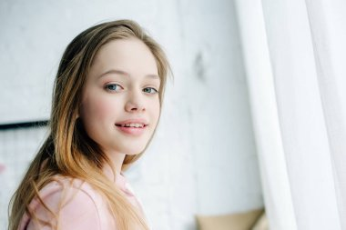 Joyful teenage kid in pink hoodie looking at camera with smile stock vector