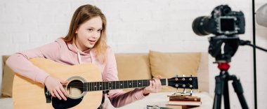 Panoramic shot of teenage blogger playing acoustic guitar in front of video camera