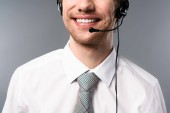 cropped view of smiling call center operator in headset