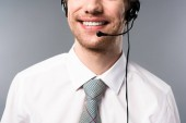 partial view of smiling call center operator in headset