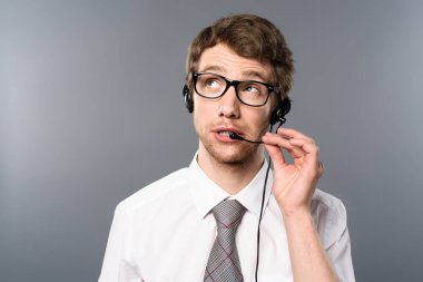 dreamy call center operator in headset and glasses looking away on grey background