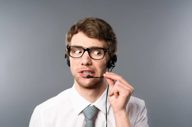 Confused call center operator in headset and glasses looking away on grey background stock vector