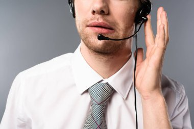 cropped view of serious call center operator touching headset