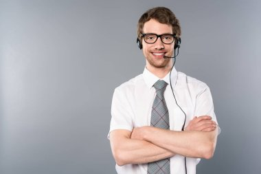 smiling call center operator in glasses and headset with crossed arms on grey background