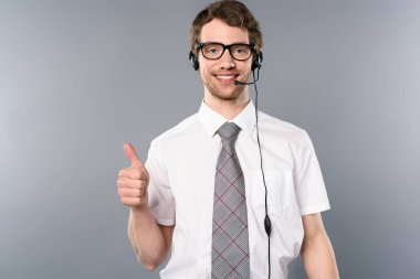 Smiling call center operator in glasses and headset showing thumb up on grey background stock vector