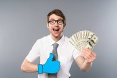 happy businessman in glasses with paper cut thumb up holding dollar banknotes on grey background