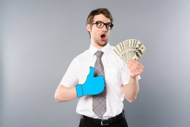 surprised businessman in glasses with paper cut thumb up holding dollar banknotes on grey background