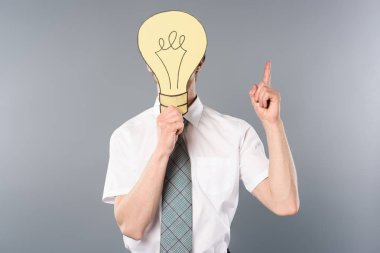 businessman holding paper cut light bulb in front of face and showing idea gesture on grey background