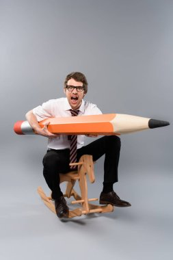 funny businessman in glasses holding huge decorative pencil, screaming and riding wooden rocking horse on grey background