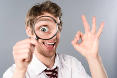 Positive businessman with funny face expression looking in magnifier and showing ok sign on grey background stock vector