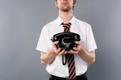 oříznutý pohled podnikatel drží vintage telefon na šedém pozadí