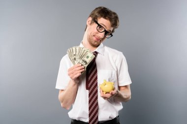 confused businessman in glasses holding piggy bank and dollar banknotes on grey background