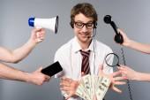Fotografia Operatore sorridente di call center in cuffia: megafono, smartphone, lente dingrandimento e telefono prendendo le banconote del dollaro