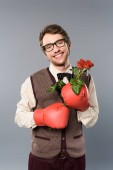 Fotografia happy man in glasses and boxing gloves holding bouquet of roses on grey background