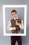 Fotografia smiling man in white frame holding bouquet of roses on grey background