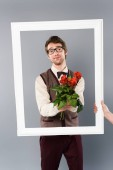 Fotografia man in white frame holding bouquet of roses on grey background